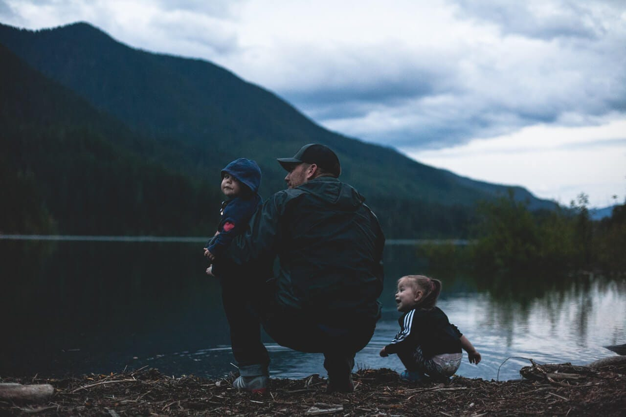 A father kneels with his young son and daughter beside a tranquil lake with mountains in the background on Father's Day.