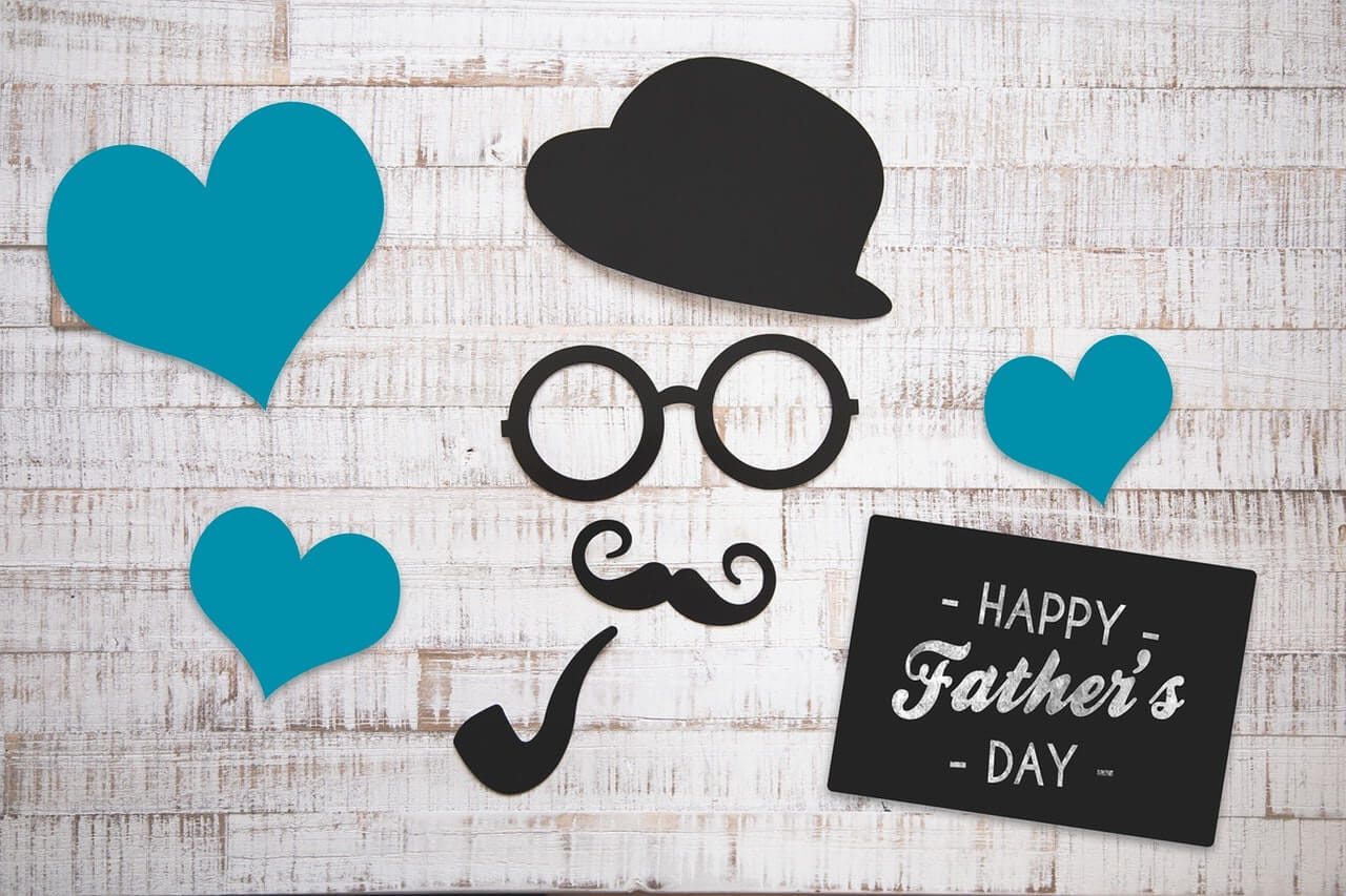 Arty image of paper cut-outs of a bowler hat, glasses, moustache and pipe suggesting a man's face surrounded by blue hearts, with a sign wishing Happy Father's Day.