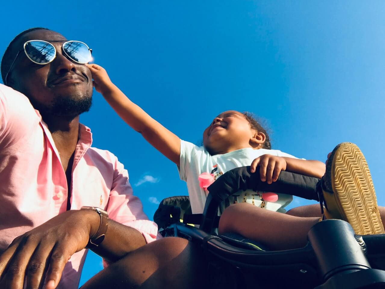A little girl in a carseat laughs as she grabs her father's sunglasses as he pulls a funny face on Father's Day.